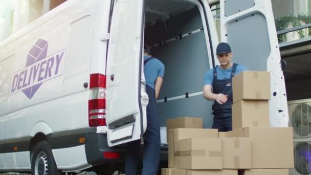 Dva silné stěhováci načítání užitkové vozidlo plné lepenkových krabic