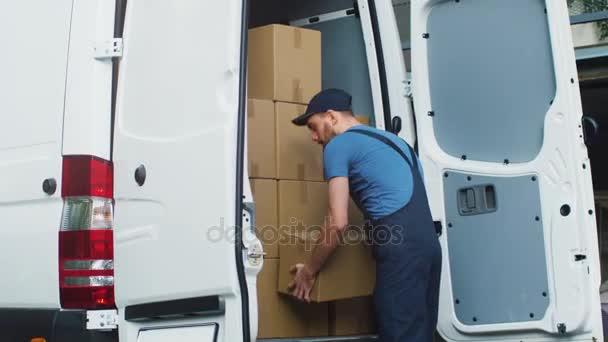 Mladí a s úsměvem dodávky služby muž bere krabici od jeho Cargo Van a procházky k dodání cíl