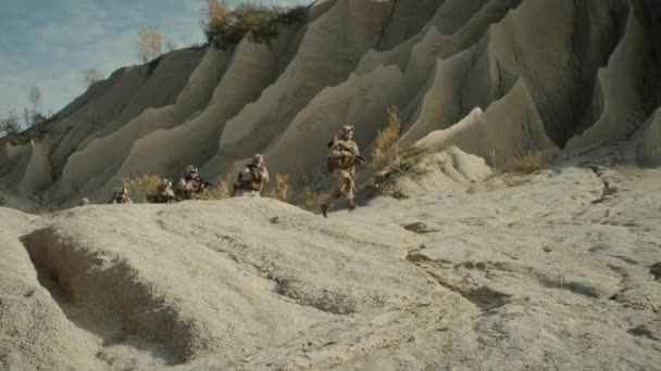 Squad of Fully Equipped and Armed Soldiers Running in the Desert. Show Motion.