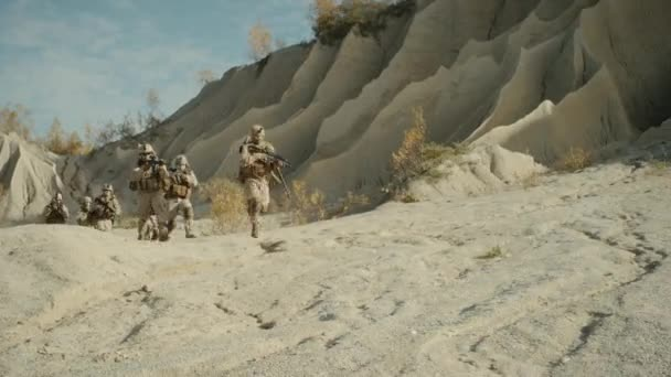 Squad of Fully Equipped, Armed Soldiers Running in the Desert.