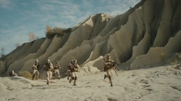 Squad of Fully Equipped, Armed Soldiers Running and Attacking During Battle in the Desert.