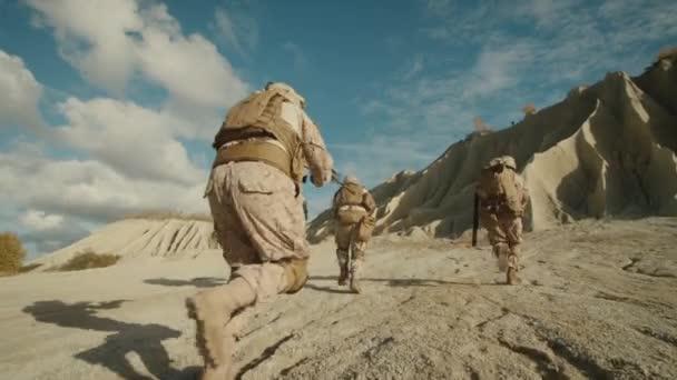 Schuss des Trupps Soldaten laufen vorwärts während der Militäroperation in der Wüste zu folgen. Slow-motion