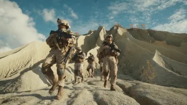 Squad of Fully Equipped and Armed Soldiers Walking down the Hill in the Desert. Slow Motion.