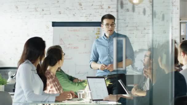 Člověk dělá tabule prezentace k jeho kreativní úředníci. Spolupracovníky sedět u stolu velké sklo s otevřenou notebooky. Kancelář je stylový a Bright. Zpomalený pohyb.