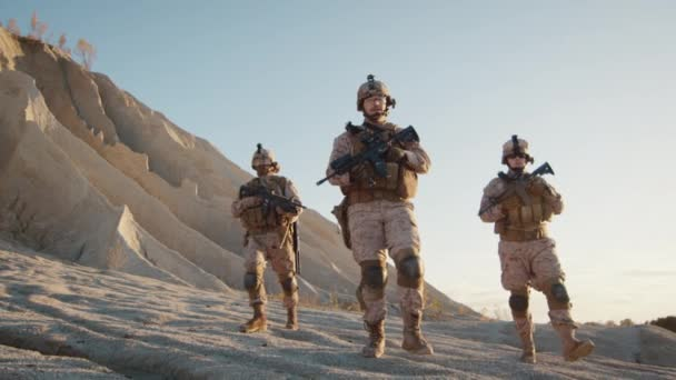 Squad of Three Fully Equipped and Armed Soldiers Walking in Desert Environment. Slow Motion.