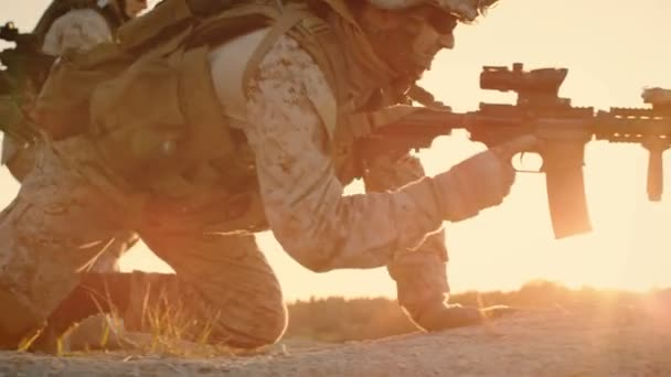 Side view Soldiers Lie Down on the Hill, Aim through the Assault Rifle Scope in Desert Environment in Sunset Light. Slow Motion.