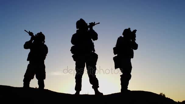 Squad of Three Fully Equipped and Armed Soldiers Standing in Desert Environment in Sunset Light. Slow Motion.