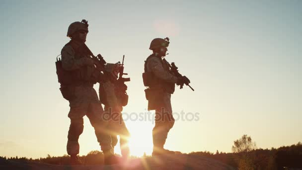 Squad of Three Fully Equipped and Armed Soldiers Standing on Hill in Desert Environment in Sunset Light. Slow Motion.