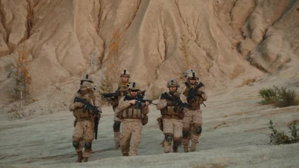 Squad of Fully Equipped and Armed Soldiers Walking Forward towards Camera in Desert Environment.