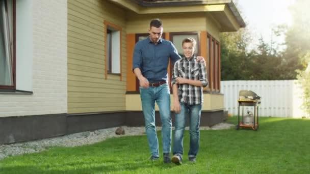 Otec a syn chodit a mluvit ve dvoře.