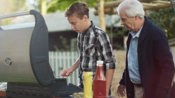 Dědeček a Grandon jsou vaření hamburgerů na grilu za jasného letního dne
