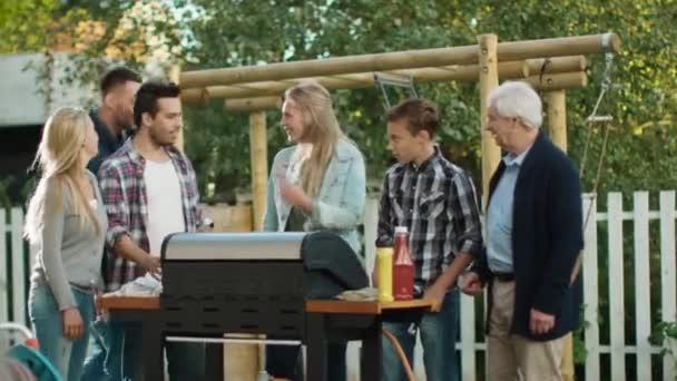 Skupina Smíšené rasy lidí se shromažďují kolem grilu na dvorku před rodinou večeří
