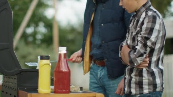 Otec a syn jsou hamburgery společné vaření za jasného letního dne