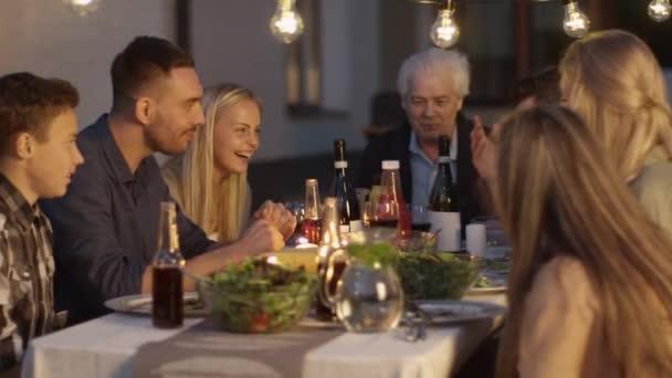 Skupina lidí, kteří sedí u stolu, jíst, komunikaci a Bavíte se během večeře rodinné sešlosti