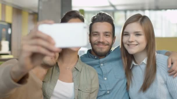 Group of Young Smiling Mixed race People Doing Selfie with Phone in Coffee Shop.