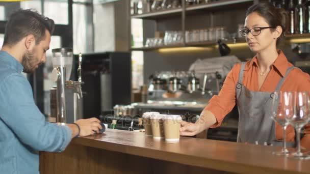 Pohledný mladý muž platit za s sebou kávu s kreditní kartou v kavárně.