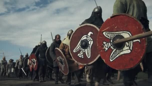 Crowd People Dressed Like Medieval Warriors with Shields Walking Forward. Medieval Reenactment.