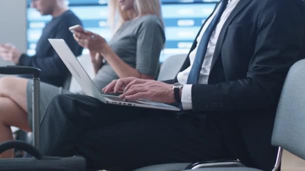 Geschäftsmann arbeitet am Laptop, während er in der Abflughalle am Flughafen auf sein Boarding wartet.