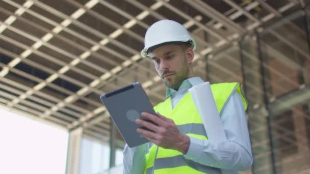 Mužské inženýr pomocí tabletový počítač. Skleněná budova nebo mrakodrap ve výstavbě na pozadí