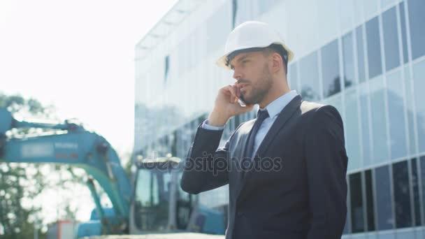 Podnikatel v tvrdý klobouk mluví po telefonu na staveništi.