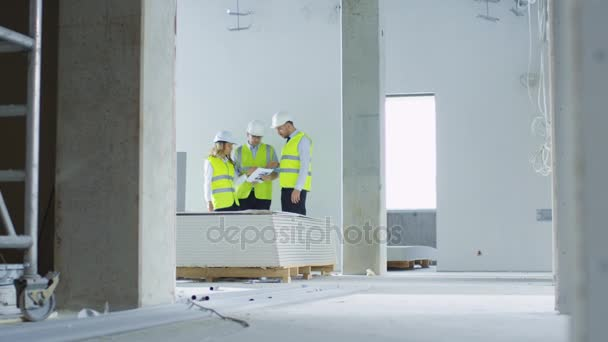 Team of Engineers in Hard Hats Having Conversation, Looking at Blueprint, inside Building Under Construction.