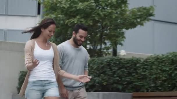 Young Smiling Woman And Man are Walking and Talking in Urban Environment.
