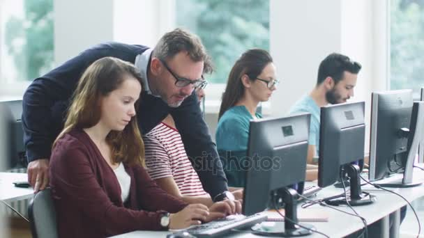 Teacher Helps Students in Computer Class During Lecture.