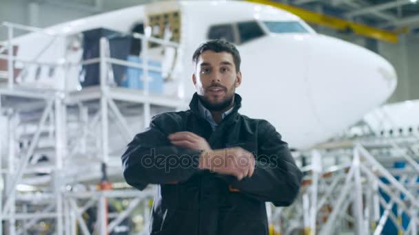 Portrét mechanik údržby letadel v hangáru. Letadlo na pozadí