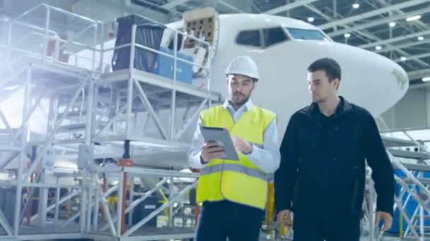 Tým mechaniky údržby letadel pohybuje do hangáru. Podržením tabletového počítače
