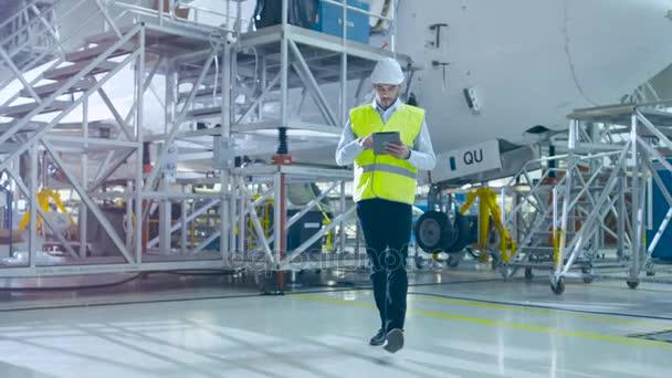Ingenieur bewegt sich durch Flugzeugwartungsterminal und grüßt einen Mechaniker
