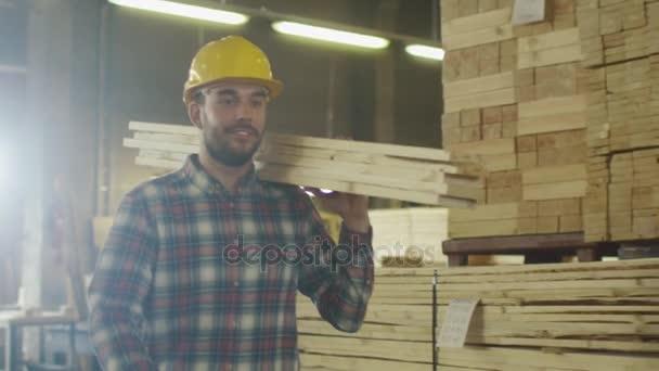Pila dělník v bezpečnostní přilba je nosili dříví do skladu při pozdravu kolegy