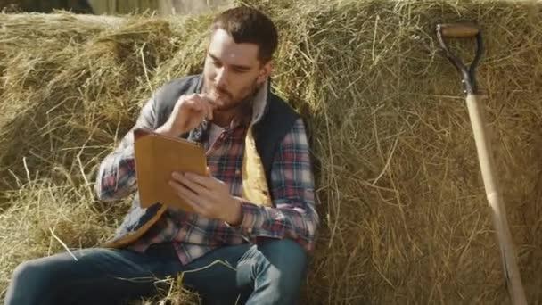 Bauer sitzt im Heu und bedient sich eines Tablet-Computers.