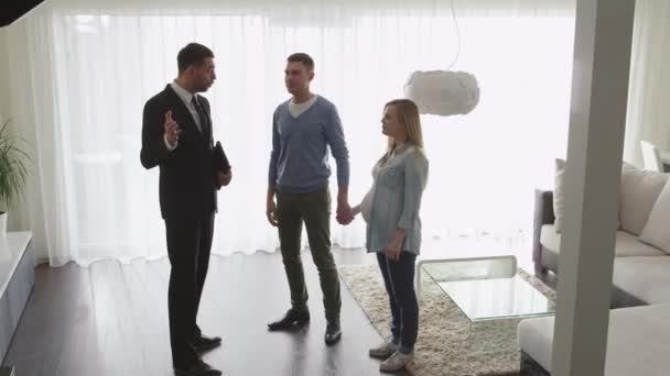 Immobilienmakler zeigt Paar neue Wohnungen Händedruck zwischen Agent und Mann.