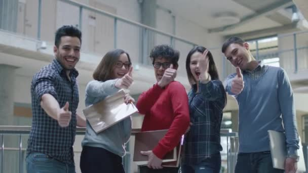 Group of happy young multi-ethnic students are showing thumbs-up in a college building.