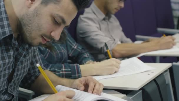 Footage of students writing with pens on paper in a collage classroom during lecture.