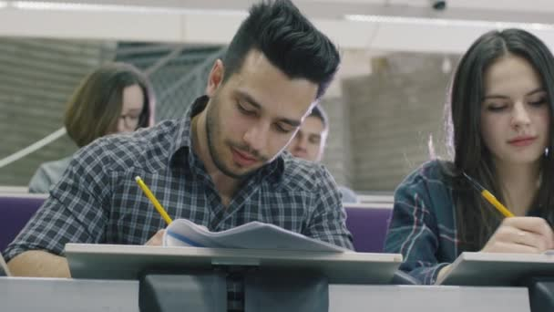Footage of latin student writing with pen on paper in a collage classroom during lecture.
