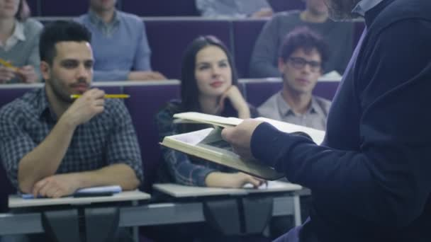 College professor is teaching a class of multi-ethnic students while holding a book.