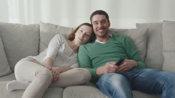 Pár sedí na gauči doma a sledování televize.