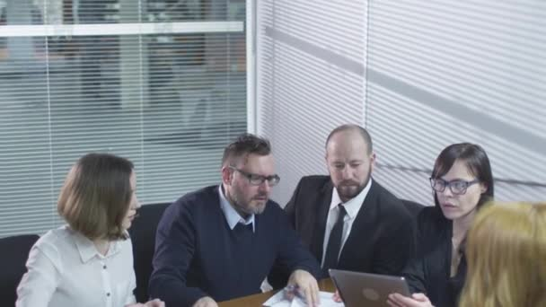 Group of employees are having a conversation in meeting room. Businesswoman is using a tablet computer.