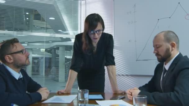 Podnikatelka dělá prezentaci pro tým zaměstnanců, kteří sedí v zasedací místnosti.
