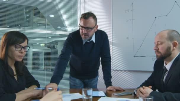 Podnikatel dělá prezentaci pro tým zaměstnanců, kteří sedí v zasedací místnosti.