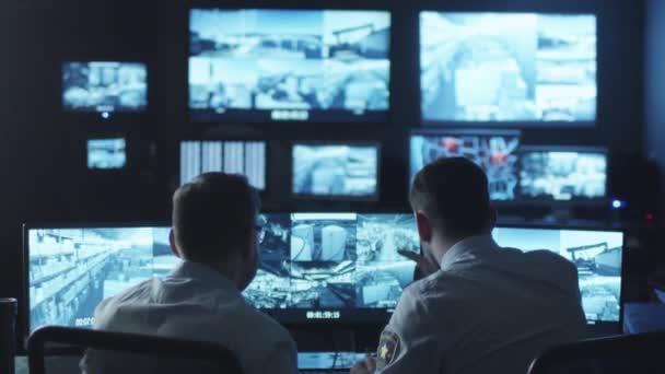 Dva bezpečnostní důstojníci si všiml vetřelcem na obrazovce počítače sledování v tmavé místnosti, sledování.