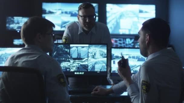Biztonsági tisztviselők csoportja, amelyek egy beszélgetés a munka egy sötét felügyeleti szobában tele bemutatás ernyőz.