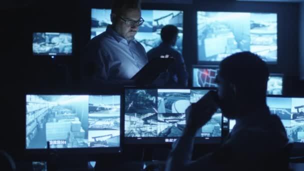 Sicherheitsbeamter benutzt einen Tablet-Computer in einem dunklen Überwachungsraum voller Bildschirme.