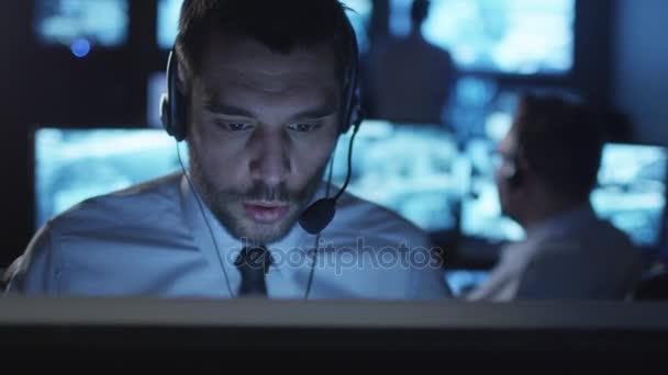 Spezialist für technische Unterstützung spricht auf einem Headset, während er an einem Computer in einem dunklen Überwachungsraum mit Bildschirmen arbeitet.