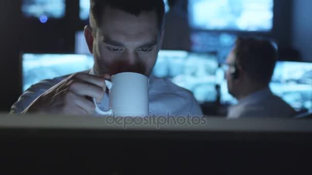 Boldog terméktámogatási szakember kávét iszik rövid idő működő-ra egy számítógép-ban egy sötét szoba monitoring tele van bemutatás ernyőz.