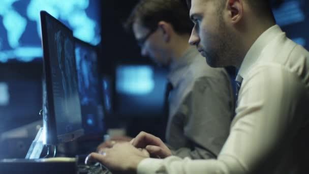 Dvě It, které programátoři pracují na počítači v tmavé kanceláři místnosti naplněné zobrazovacími jednotkami