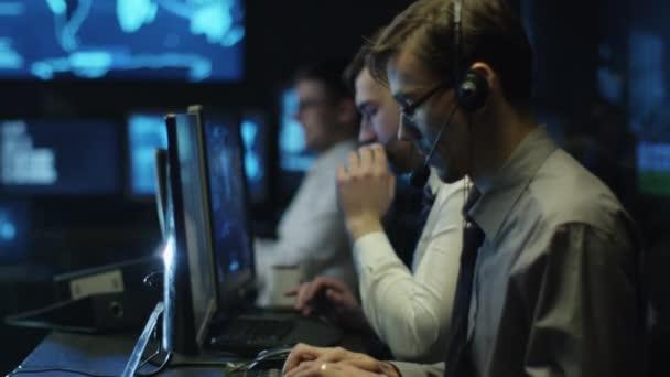 Dvě It, které programátoři pracují na počítači s mikrofonem v tmavé kanceláři místnosti plné zobrazovacími jednotkami.