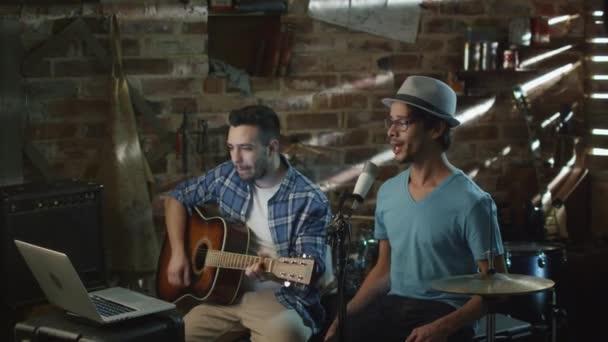 Dvě mladý muž zpívat a hrát na kytaru při nahrávání skladby v domácím studiu v garáži.