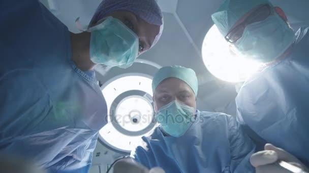 Tým lékařů a sester nad pacientem. Pacienta pohledu